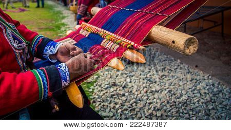 Woman hands weaving at a market in Peru