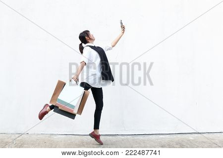 beauty asian woman hold shopping bag in right hand and smart phone in left hand