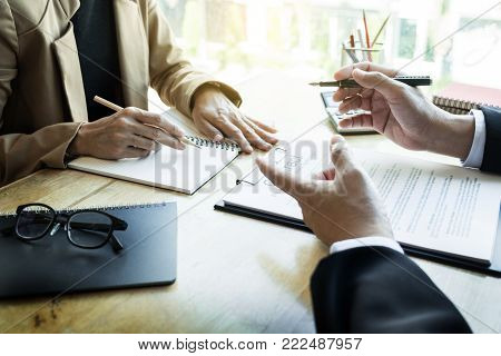 Young business team working with new startup project offering contract paper to his business partner for sign contract in conference room. discussing. Business accounting financial meeting concept.