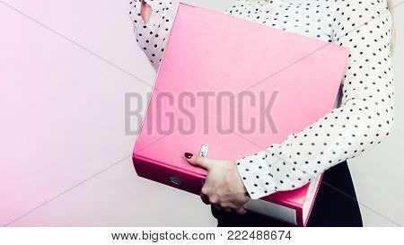 Woman hand holding pink binder with many documents. Office, bookkeeping objects concept.