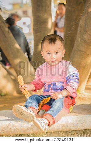 Portrait Of A Baby With A Banana On Tree Background