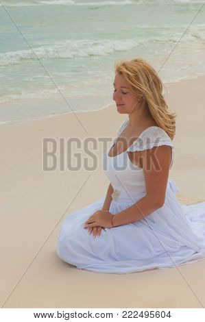 Photo Of Girl Presenting A Desire Sitting On The White Sand Of A Tropical Beach