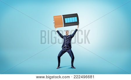 A small happy businessman smiles and holds a huge fully charged battery over his head. Energy supply. Business resources. Power for work.