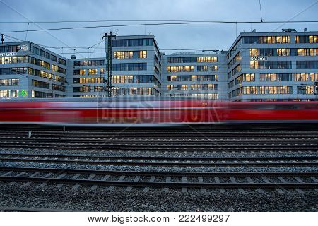 Munich,Germany-Jan 16,2018: A commuter  train streaks in front of office buidings early in  the evening