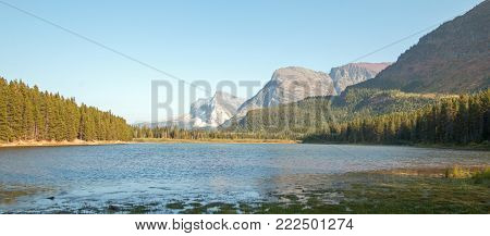 FISHERCAP LAKE ON THE SWIFTCURRENT HIKING TRAIL NEAR WILBUR CREEK IN THE MANY GLACIERS REGION OF GLACIER NATIONAL PARK DURING THE 2017 FALL FIRES IN MONTANA USA