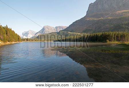 FISHERCAP LAKE ON THE SWIFTCURRENT HIKING TRAIL NEAR WILBUR CREEK IN THE MANY GLACIERS REGION OF GLACIER NATIONAL PARK DURING THE 2017 FALL FIRES IN MONTANA UNITED STATES