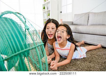 Mother Using Fan Helping Daughter Refreshing