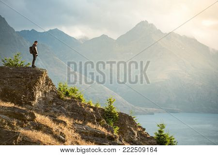 Young Asian male traveler standing on the edge of vista lookout with mountain scenery and Lake Wakatipu in background, Watching sunset in Queenstown, South Island, New Zealand