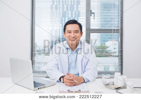 Smiling asian doctor sitting at his desk in medical office