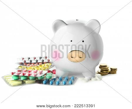 Piggy bank with pills and coins on white background. Health care concept