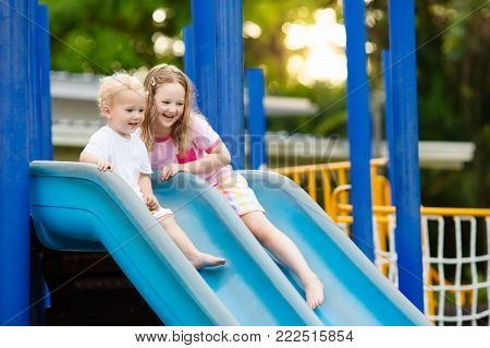 Kids on climbing and sliding on outdoor playground. Children play in sunny summer park. Activity and amusement center in kindergarten or school yard. Child on colorful slide. Toddler kid outdoors.
