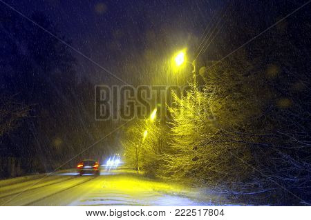 Winter in city by night with snow-flurry weather. Difficult driving conditions.