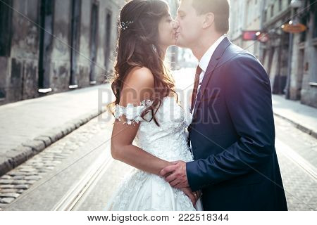 Charming newlyweds are holding hands and kissing during the susent. Sensitive outdoor portrait
