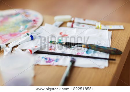 fine art, creativity and artistic tools concept - palette knife, brushes, paint tubes and paper tissue on table