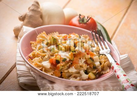 pasta with tomatoes zucchinis and scamorza cheese, selective focus
