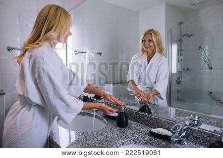 beautiful middle aged woman in bathrobe washing hands in hotel bathroom