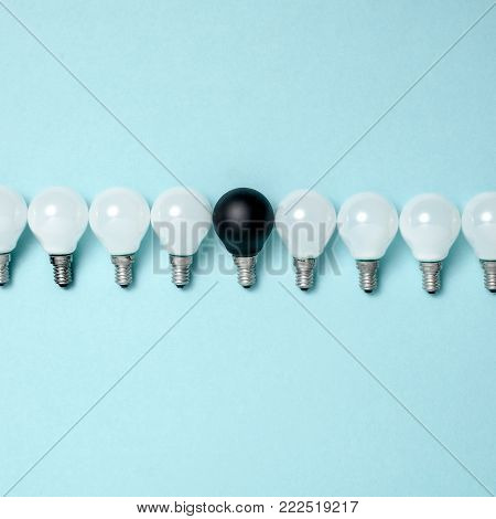 Creativity, creative thinking, ideas concept with electric lamps on blue background. The concept - not like everyone else or concept difference or individuality