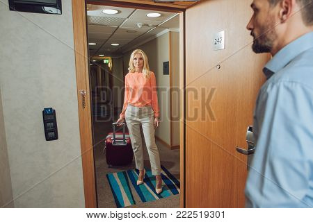 beautiful mature woman with suitcase standing in hallway while bearded man opening door in hotel room