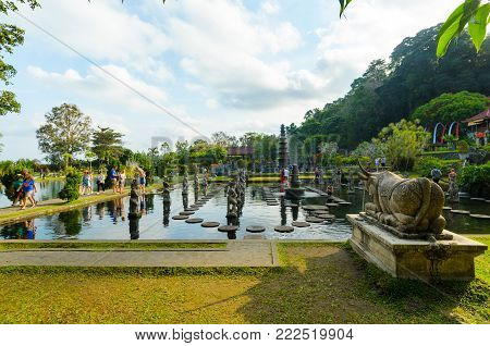 TIRTANGGA, INDONESIA - 28 AUG 2014: Tourists flock the Tirtagangga temple's gardens, its stone causeway and fountains, in Bali, Indonesia