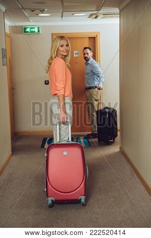 mid adult couple with suitcases looking at camera while walking in hotel hallway