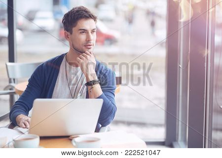 Deep in thoughts. Enigmatical bearded man putting elbows on the table and sitting in front of his computer while looking aside