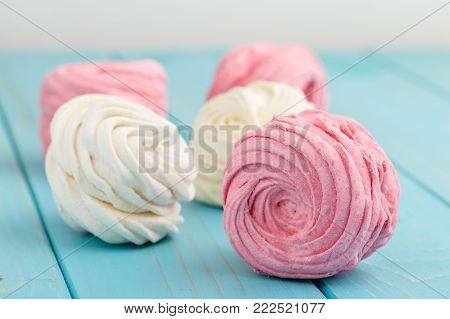 Homemade white and pink zephyr or marshmallow on blue wooden background. Marshmallow, Meringue, Zephyr