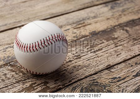 Baseball ball on old rustic wooden backstage .