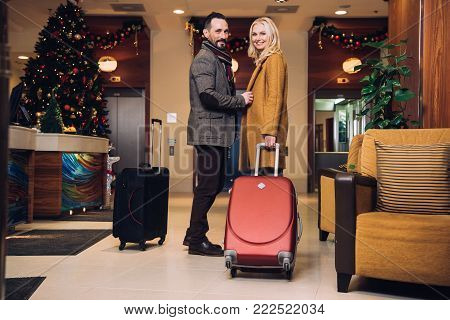 middle aged couple standing with suitcases and smiling at camera in hotel hallway at christmas