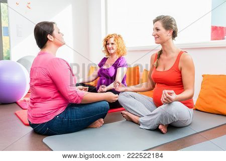 Midwife coaching expectant mothers during relaxation exercises in prenatal class