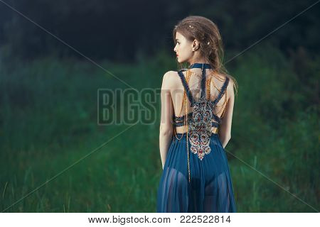 Elf. Beautiful girl in magic forest. Fantasy young woman in woods outdoors at night. Creative portrait of young model in fantastic costume. Back view.