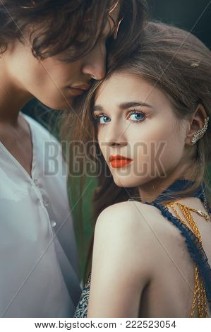 Young couple of elves in love standing in magical forest outdoor on nature. Close-up portrait. Fairy tale love, relationship and magic people concept. Man lovely ambracing woman