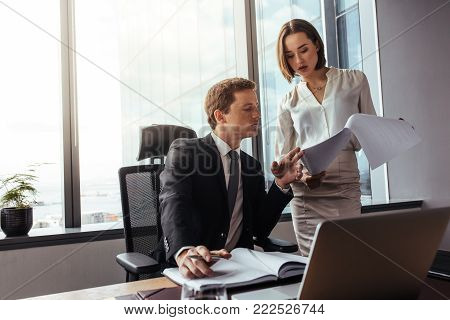 Business team of three planning work in office, with female colleague explaining her strategy to boss. Business professionals working together on new project in modern office.