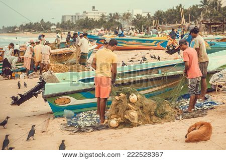 NEGOMBO, SRI LANKA - DEC 21, 2017: Fishermen upload their nets into boats for fishing in the Indian Ocean on December 21, 2017. Negombo with population of 150.000 known for its fishing industry
