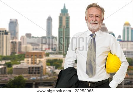 Caucasian Businessman Architect or Engineer, Holding Hard Hat or Helmet, Standing beside Modern City Building on Construction site as Real Estate or Land Project Development Executive or Manager Business Concept.
