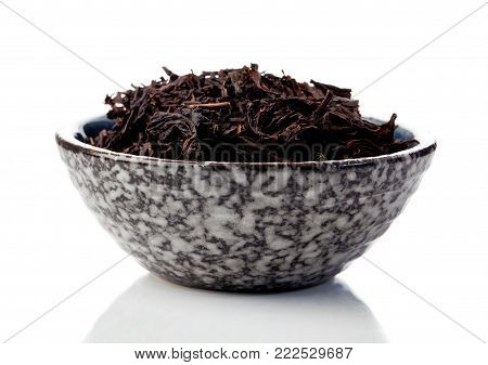 black tea leaves in a cup on a white background