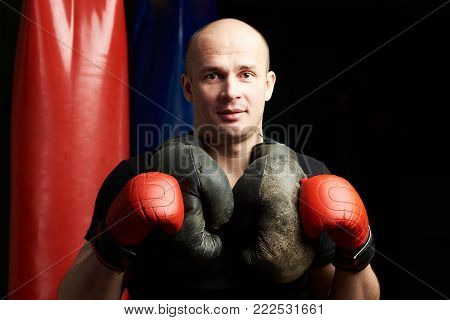 Headshot of young man boxer in red gloves on gym background
