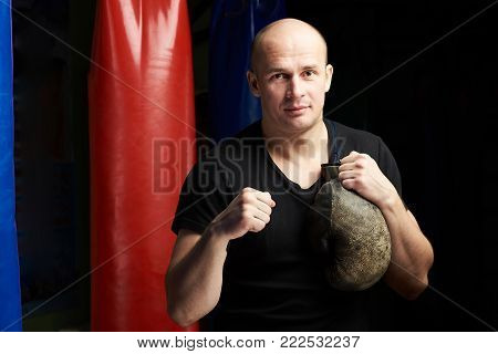 Boxing exercise concept. One young bold caucasian man hold fist up