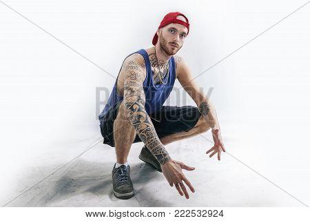 Standing Tattooed Rap Singer Posing In Studio