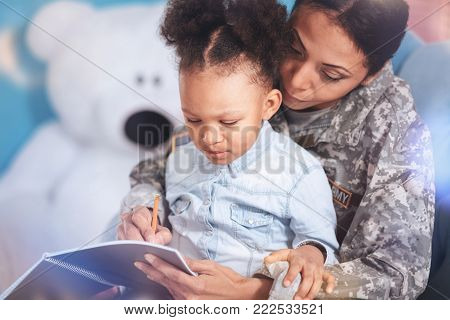 Time for studying. Positive smart nice woman holding a notebook and writing in it while studying with her daughter