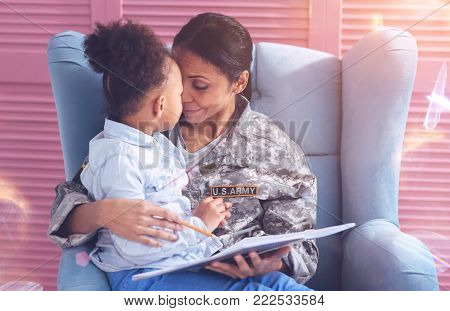 School home task. Joyful positive nice woman holding notes and looking at her daughter while doing school home task