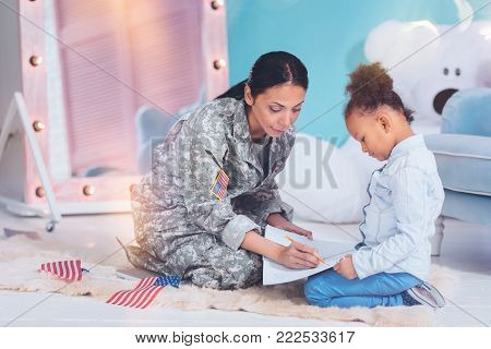 School assignment. Cute nice smart girl sitting near her mother and looking at the notes while doing her school home task