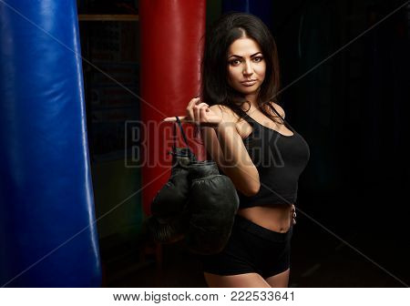 Sexy brunette with boxing gloves posing on sand bags background