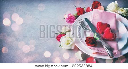 Valentines day table setting with plate, roses, red ribbon and hearts. Holidays background. Valentines day background