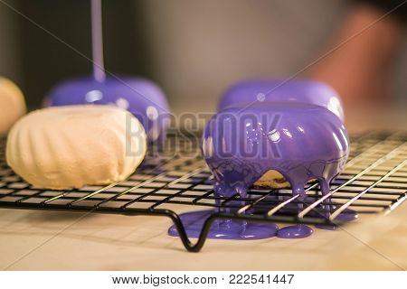 The purple icing on the cakes. Modern French mousse desserts with mirror glaze. Picture for a menu or a confectionery catalog. poster