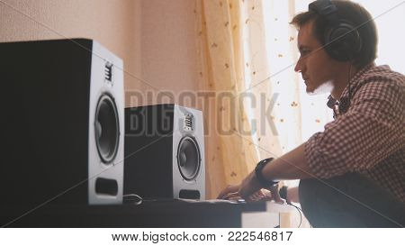 Young man composer composes music on the computer, sound engineer working, profile view