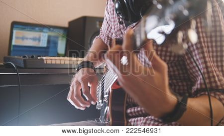 Young musician composes and records music playing the electric guitar, using computer and keyboard, focus on hands