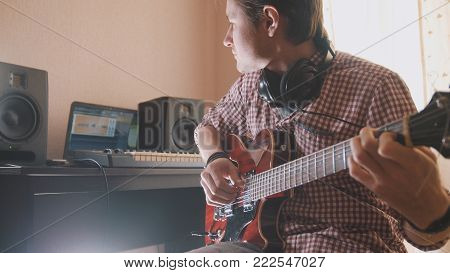 Young musician composes and records soundtrack playing the guitar, using computer, headphones and keyboard, focus on equipment