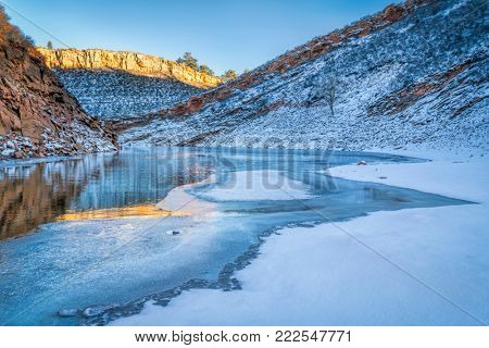 calm winter sunset over partially frozen Horsetooth Reservoir near Fort Collins in northern Colorado