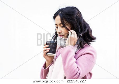 Beautiful young asian woman drinking hot drink from disposable paper cup outdoors on white background. Look down. Girl touches her hair.