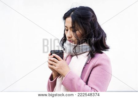 Beautiful young asian woman drinking hot drink from disposable paper cup outdoors on white background. Look down. Girl dressed in pink coat and white scarf.